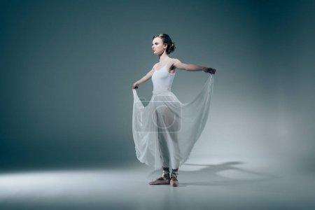 elegant ballerina standing in white dress