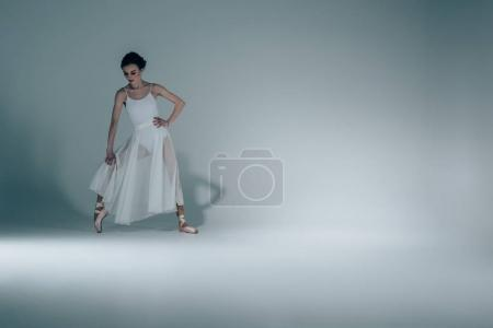 elegant ballerina in white dress stretching in studio
