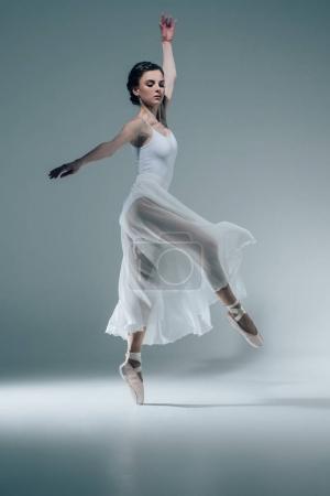 elegant ballerina in white dress dancing in studio