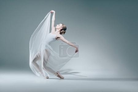 Photo for Attractive ballerina dancing in white dress - Royalty Free Image