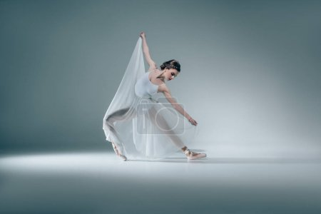 elegant beautiful ballerina dancing in white dress