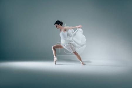 elegant ballerina dancing in white dress