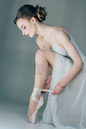 ballerina wearing ballet shoes on feet, isolated on grey