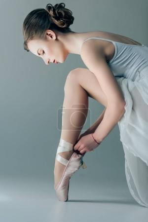 beautiful dancer wearing ballet shoes on feet, isolated on grey