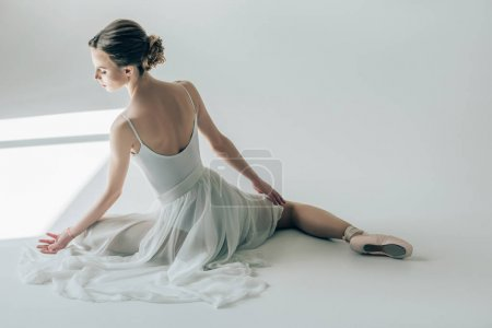 rear view of ballerina sitting in white dress and ballet shoes