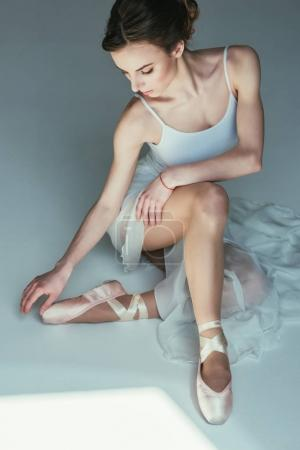 beautiful ballerina sitting in white dress and ballet shoes