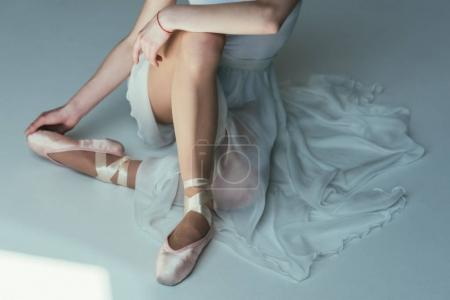 cropped view of tender ballerina sitting in white dress and ballet shoes