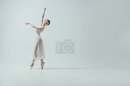 attractive ballerina in white dress dancing in studio, isolated on white