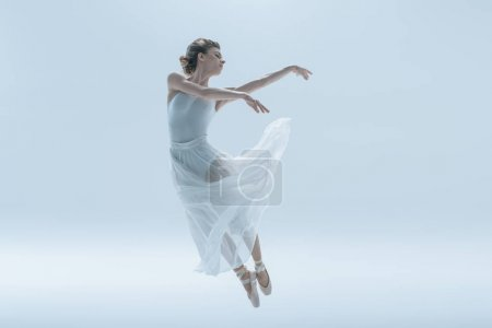 young ballerina in white dress jumping in studio, isolated on white
