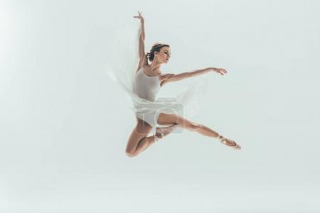 young elegant ballerina in white dress jumping in studio, isolated on white