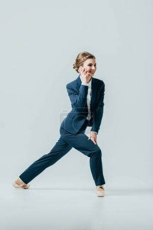 businesswoman in suit and ballet shoes talking on smartphone, isolated on grey
