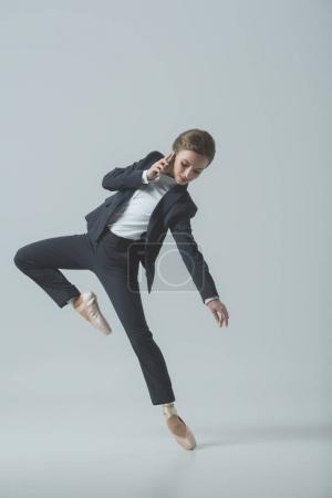businesswoman in suit and ballet shoes dancing and talking on smartphone, isolated on grey