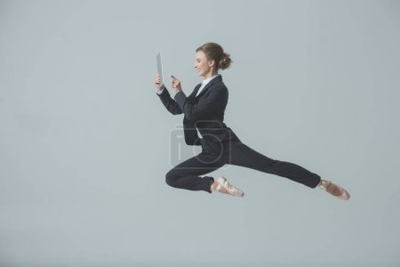Photo for Businesswoman in suit and ballet shoes jumping and using digital tablet, isolated on grey - Royalty Free Image