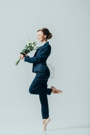 happy businesswoman in suit and ballet shoes with bouquet of flowers, isolated on grey