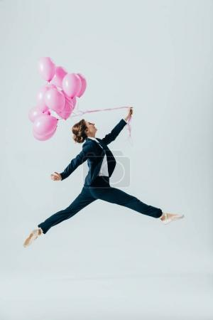 businesswoman in suit and ballet shoes jumping with pink balloons, isolated on grey