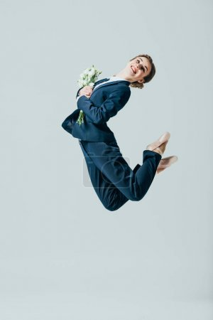 businesswoman in suit and ballet shoes jumping with bouquet of flowers, isolated on grey