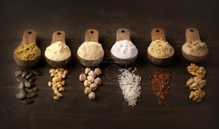 Photo for Gluten free flours in wooden spoons on a brown background - Royalty Free Image
