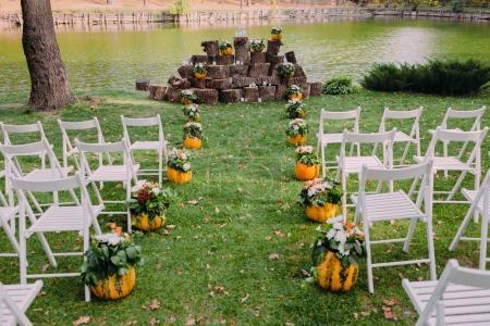 Photo pour Décoration de mariage avec citrouilles et fleurs d'automne. Cérémonie en plein air dans le parc. Chaises blanches pour invités. Gros plan - image libre de droit