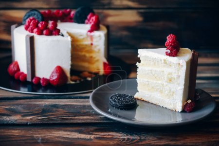 Photo for Slice of cake topped with strawberries and chocolate cookies on the wooden background. Soft focus on the slice of pie. Artwork. - Royalty Free Image