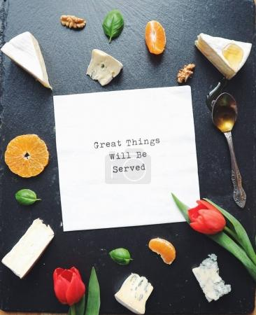 Assorted cheese on a black stone table. Top view. Gourmet cuisine. Delicious food. Card with text Great things will be served