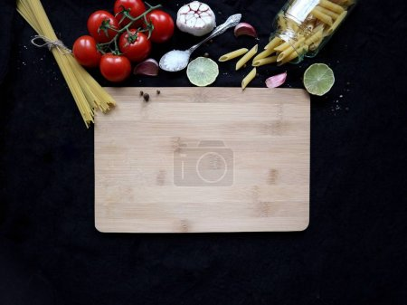 Photo for Wooden cutting board and raw ingredients for cooking: pasta, cherry tomatoes, garlic, lime, salt. Food background with copy space. Flat lay - Royalty Free Image