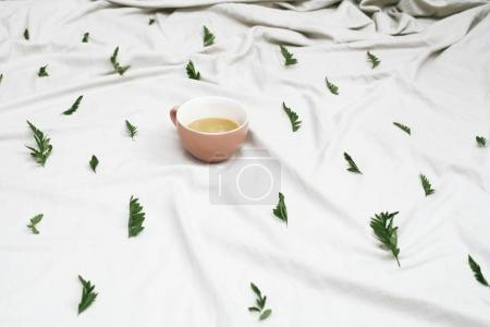 Mug on white cloth with leaves