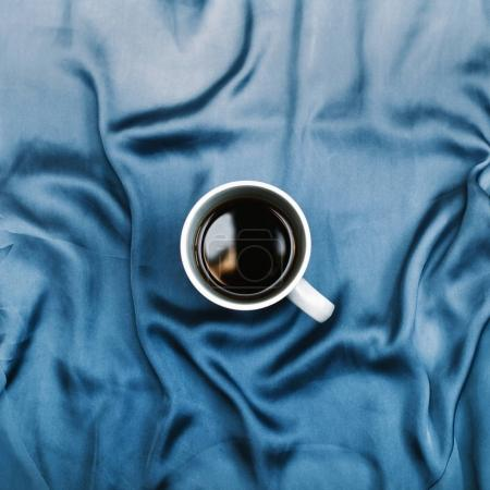 White mug on blue cloth
