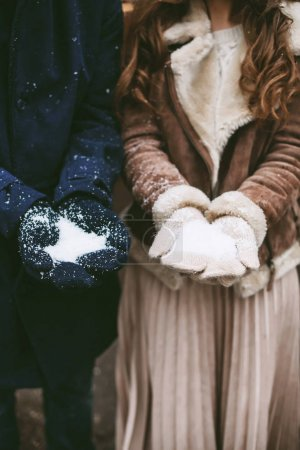 Young happy couple holding snow