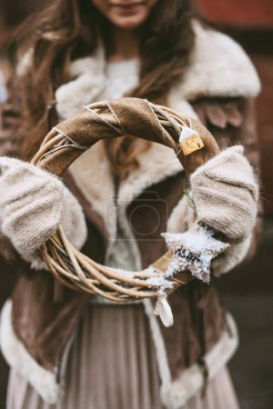 Photo for Woman in warm winter clothes and knitted mittens holding natural wreath - Royalty Free Image