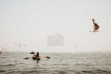 Photo pour Rivière Ganges dans le brouillard, un bateau et les oiseaux volant - image libre de droit