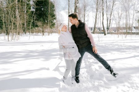 Lovely couple together playing with snow outdoors on a sunny day. Pretty woman and attractive man wearing stylish casual clothes laughing and smiling each other.