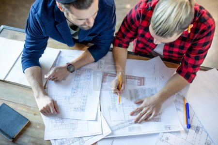 Photo for Overhead view of two young male architects discussing blueprints - Royalty Free Image