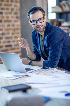 Foto de Retrato de hombre de negocios joven sonriente sentada con ordenador y mirando a cámara - Imagen libre de derechos