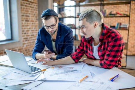 Arquitectos usando laptop y smartphone