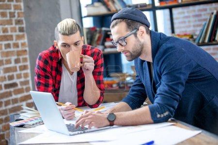 Photo pour Deux jeunes designers masculins travaillant au projet tout en utilisant un ordinateur portable et en buvant du café - image libre de droit