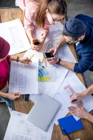 Photo for Overhead view of young male and female designers working at project with blueprints - Royalty Free Image