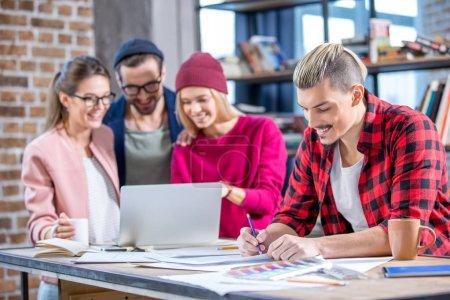 Photo pour Jeune homme souriant prenant des notes tandis que ses collègues de travail sur ordinateur portable - image libre de droit