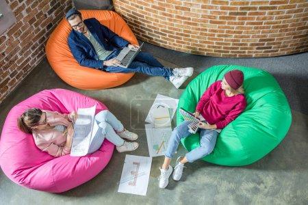 Photo pour Vue de dessus de jeunes designers ou architectes travaillent tout en étant assis dans les fauteuils-sacs - image libre de droit
