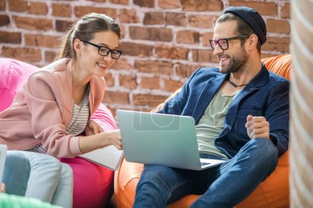 Photo for Young man and woman using laptop while sitting in bean bag chairs - Royalty Free Image
