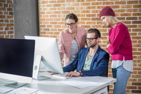 Photo pour Trois jeunes gens d'affaires confiants qui travaillent avec l'ordinateur - image libre de droit