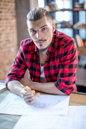Photo pour Portrait de jeune architecte masculin assis à table avec des plans et regardant la caméra - image libre de droit