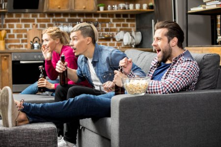 Photo for Excited male and female friends drinking beer and eating popcorn on couch - Royalty Free Image