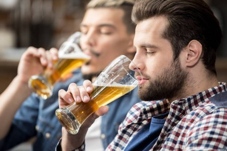 Photo for Two young male friends drinking beer - Royalty Free Image