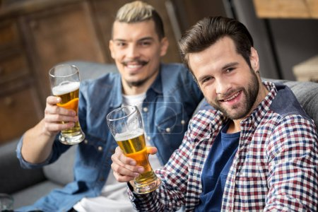 Photo for Happy male friends drinking beer and looking at camera - Royalty Free Image