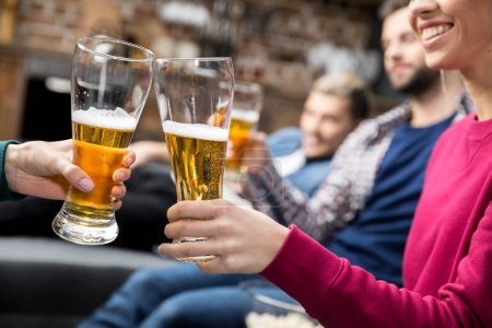 Photo for Close-up partial view of young friends drinking beer at home - Royalty Free Image