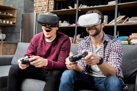 Photo for Male friends playing vigeo game in virtual reality glasses - Royalty Free Image