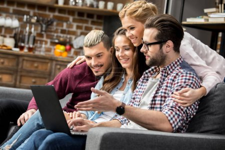 Photo for Four young friends using laptop while sitting on sofa - Royalty Free Image