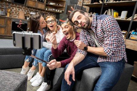 Photo pour Jeunes amis heureux prenant selfie drôle dans le salon - image libre de droit