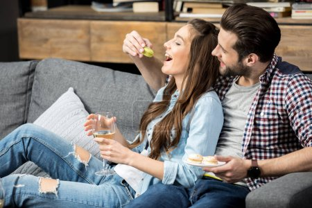 Photo for Young couple in love drinking wine and eating sweets - Royalty Free Image