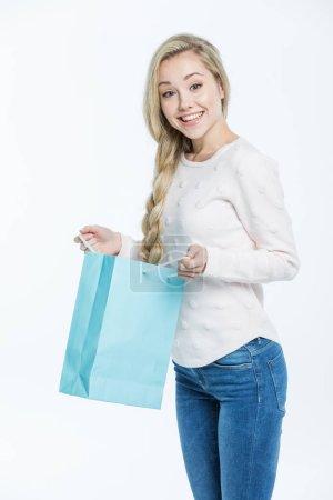 Photo pour Joyeux jeune femme avec sac à provisions souriant à la caméra isolée sur blanc - image libre de droit